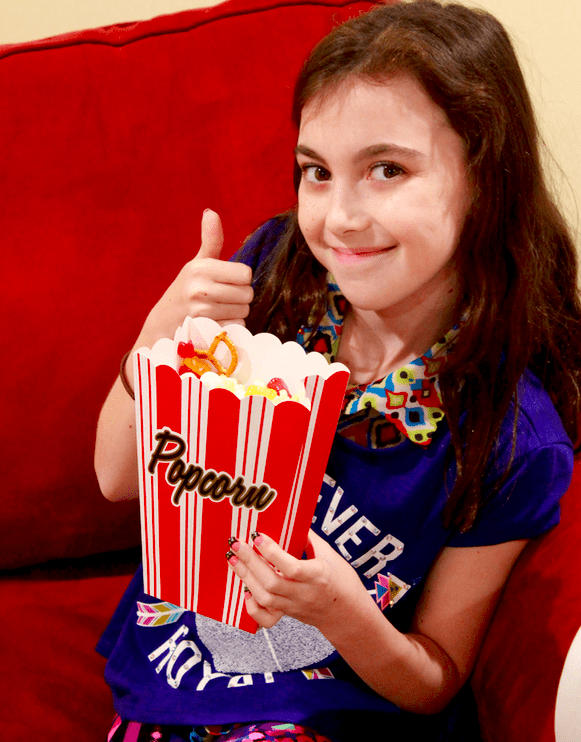 A school aged girl eating popcorn