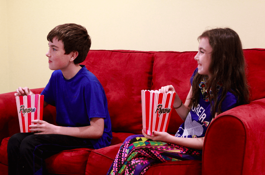 two kids eating popcorn while watching a movie