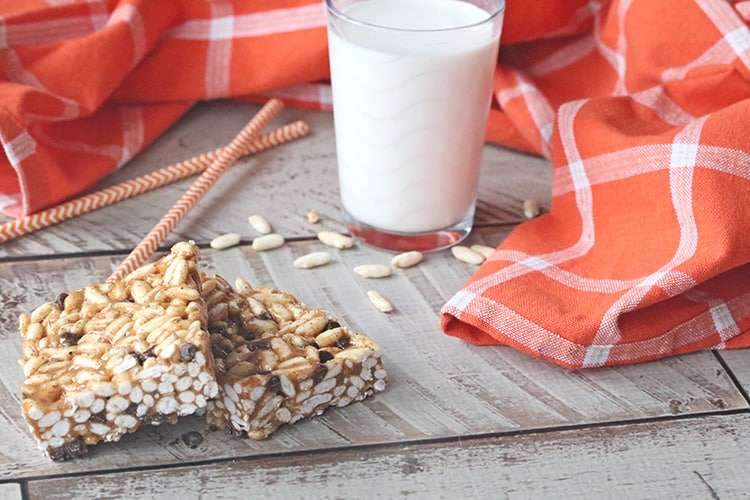 Two healthy rice krispies treats bars next to a glass of milk