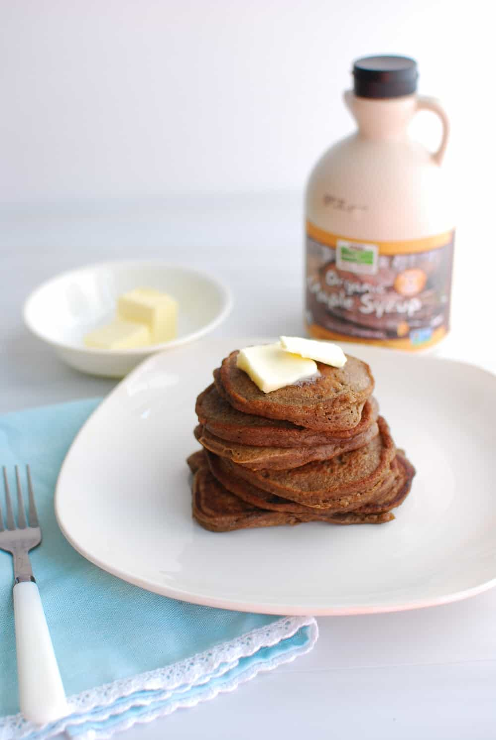 Grain free banana flour pancakes next to butter and maple syrup