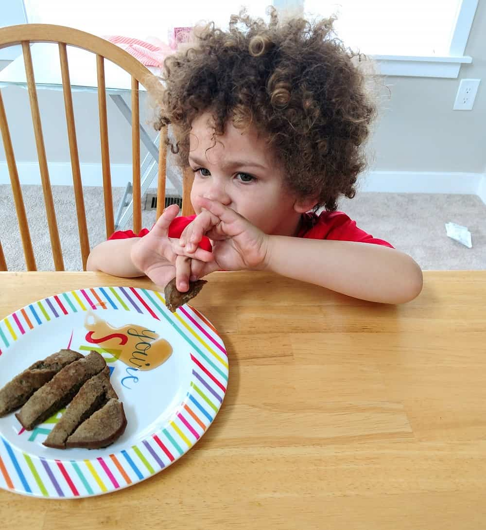 Little boy eating banana flour pancakes