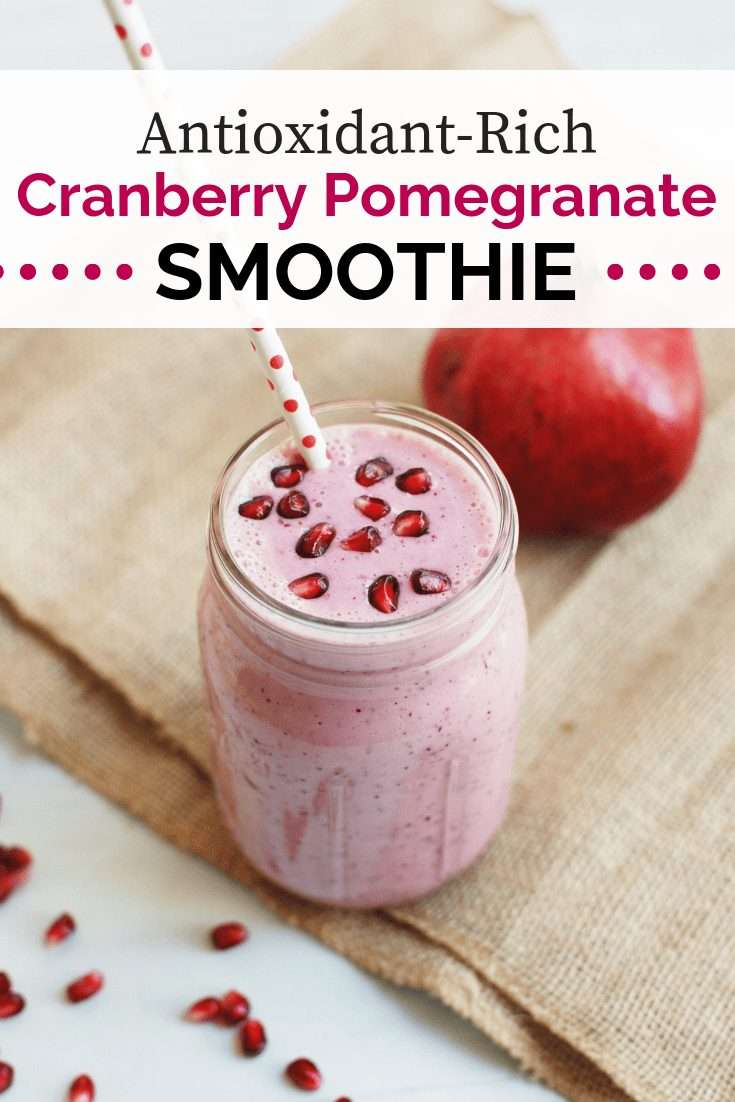 Cranberry smoothie in a mason jar topped with pomegranate arils
