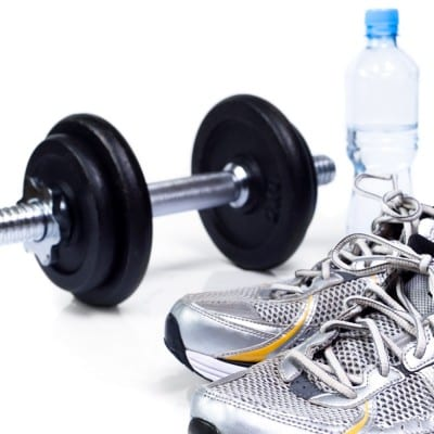 A pair of shoes next to a dumbbell to suggest how to burn 100 calories